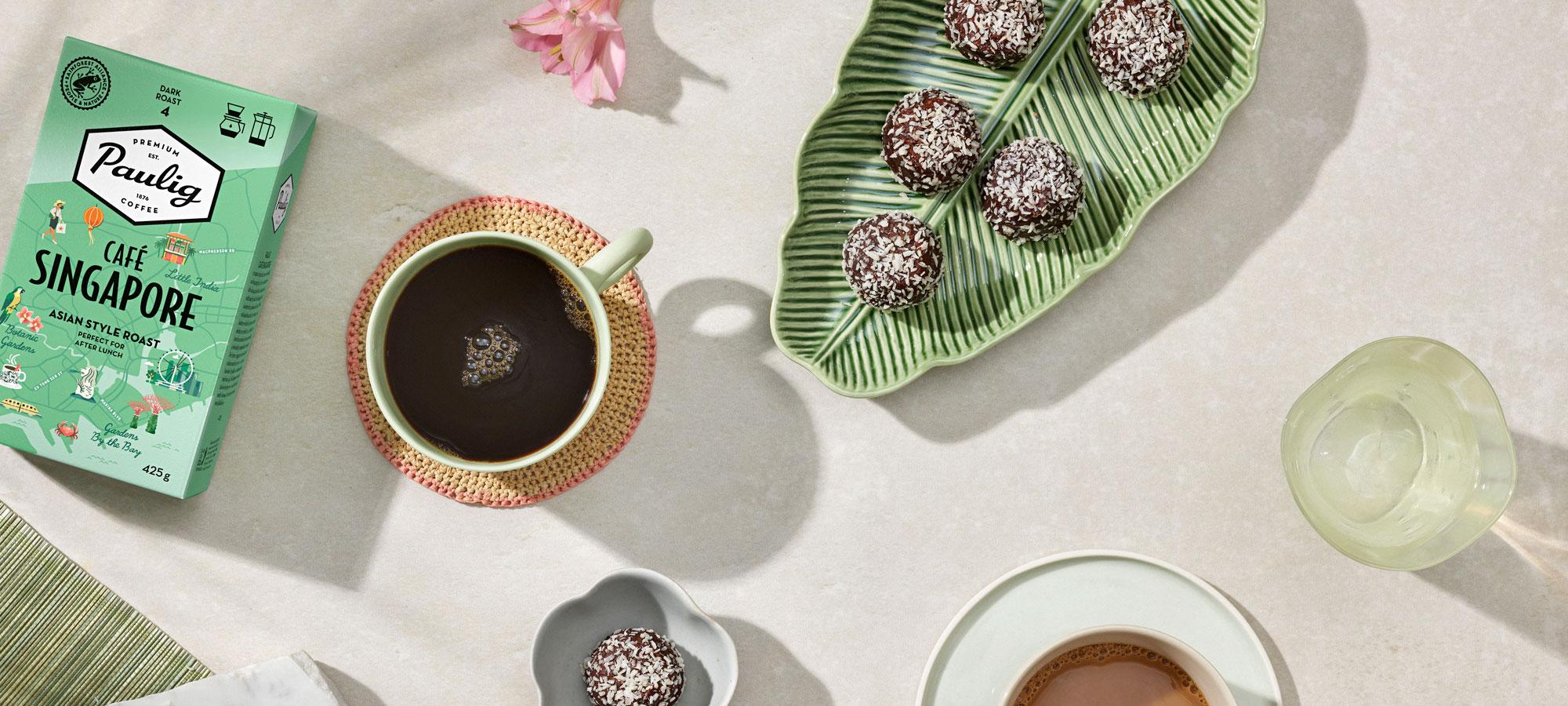 Café Singapore -kahvipakkaus ja kaakaoleivonnaisia pöydällä