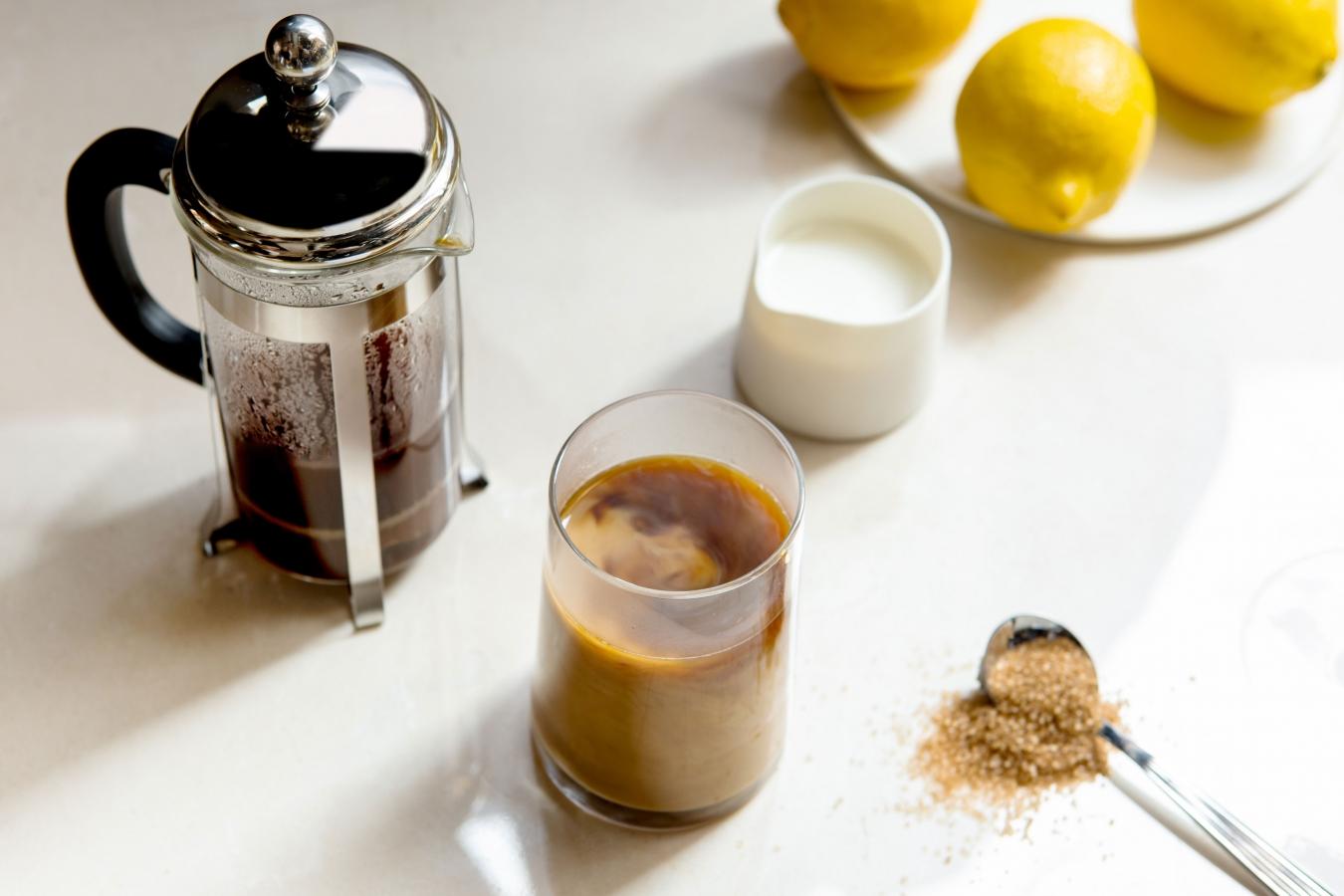 Pöydällä kahvin valmistukseen tarvittavat välineet: pressopannu, maitokannu, kahvimuki ja lusikallinen sokeria.