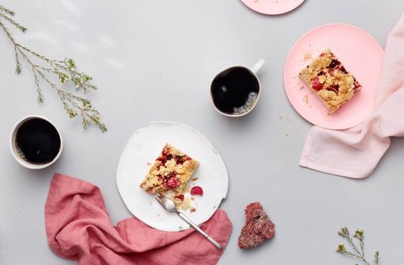 Raparperipiirakka ja kahvia tarjolla pöydällä, jossa pinkkejä somisteita
