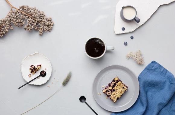 Mustikkapiirakkaa ja kahvia tarjolla pöydällä, jossa sinisiä somisteita